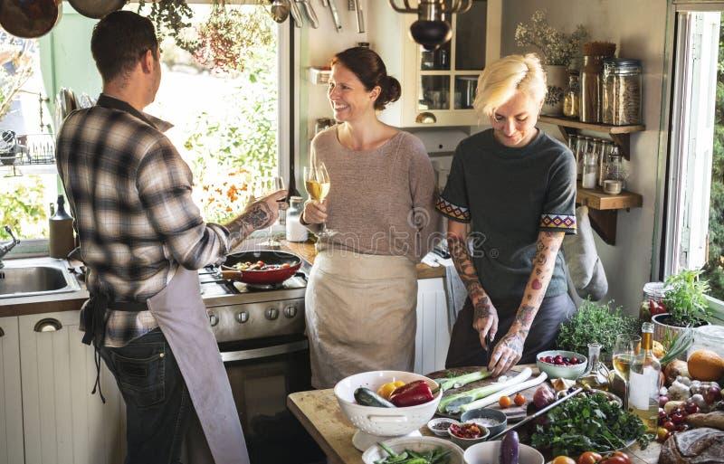 Amigos que comen el vino blanco mientras que cocina imagen de archivo