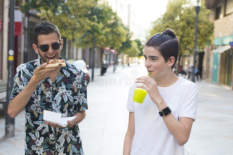 Amigos que comen en la calle foto de archivo libre de regalías