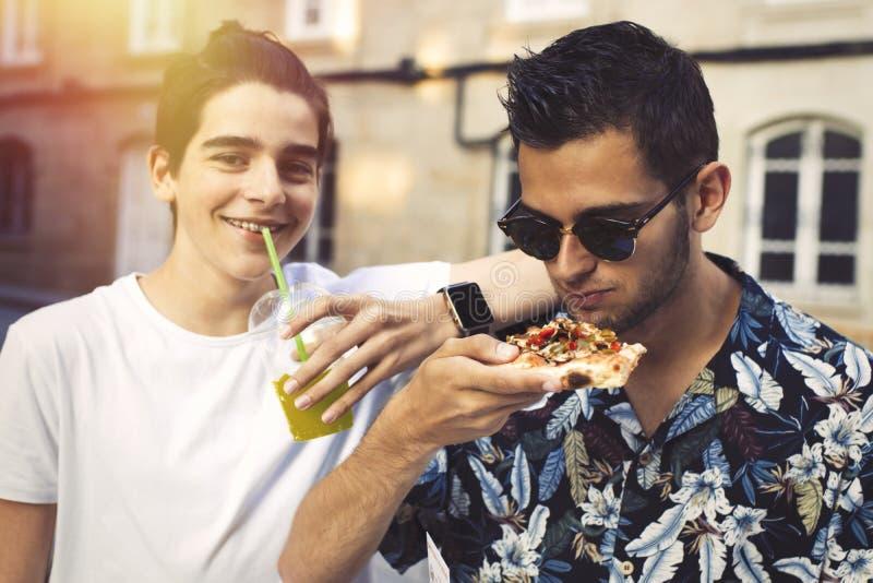 Amigos que comen en la calle fotos de archivo