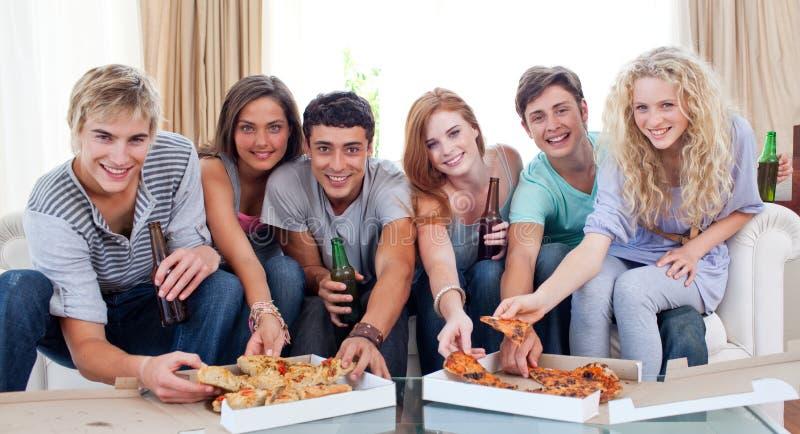 Amigos que comen la pizza en el país imagenes de archivo