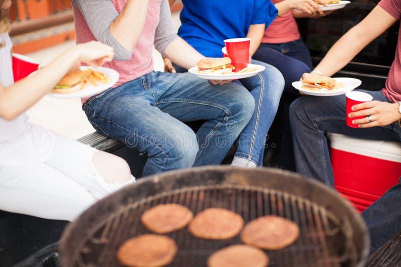 Amigos que comen las hamburguesas en una barbacoa fotografía de archivo