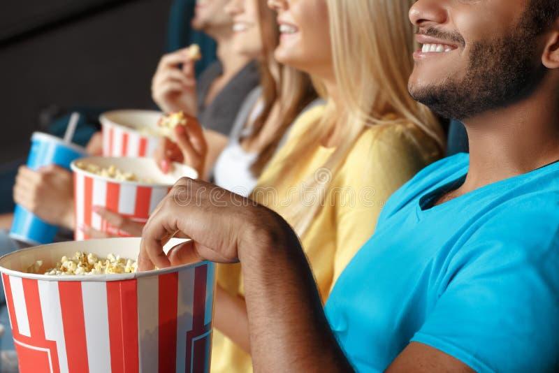 Amigos que comen las palomitas en el cine fotografía de archivo libre de regalías