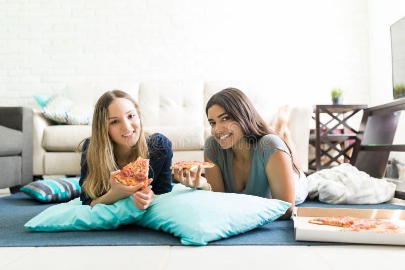 Amigos que comen pizza mientras que pasa el tiempo de la calidad junto foto de archivo libre de regalías