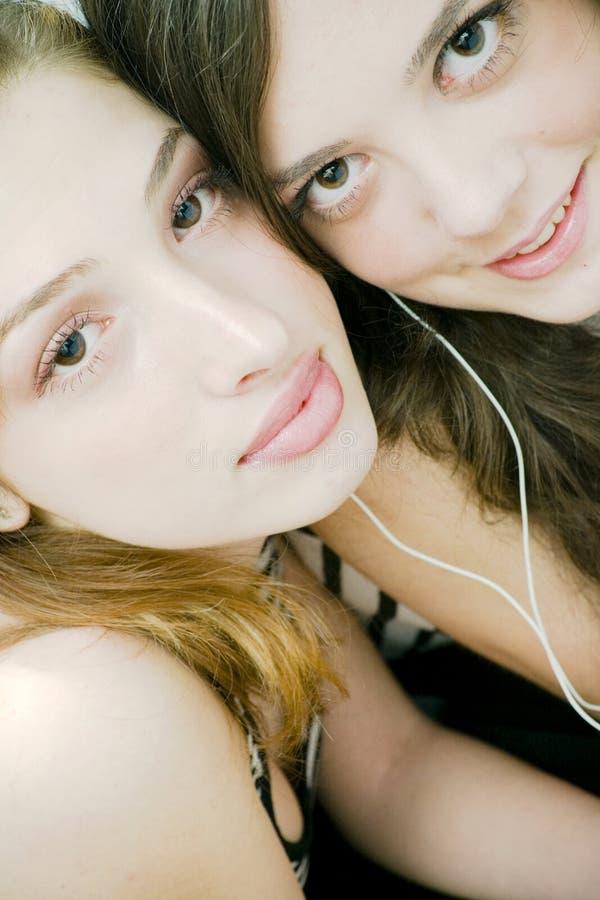 Amigos que comparten los auriculares imagen de archivo