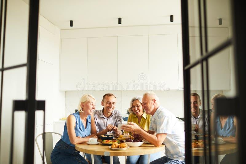 Amigos que compartilham de histórias na mesa de cozinha imagem de stock royalty free