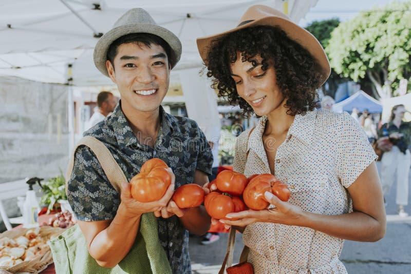 Amigos que compram tomates frescos em um mercado dos fazendeiros fotografia de stock royalty free
