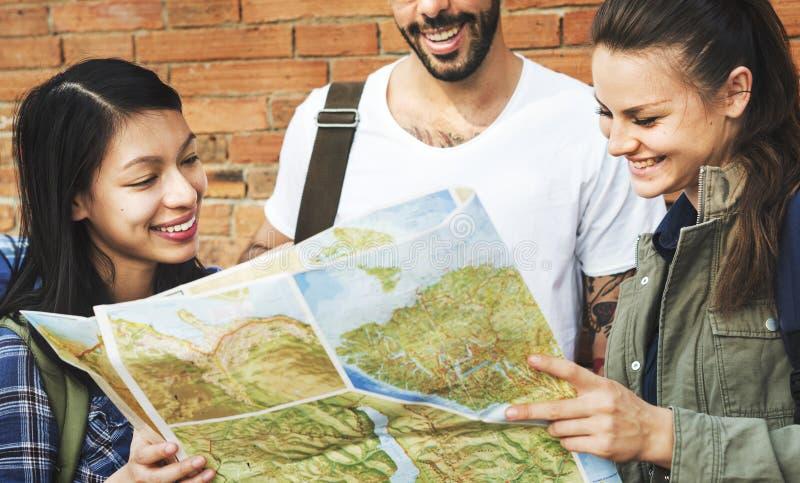 Amigos que comprueban el mapa para saber si hay direcciones imagen de archivo libre de regalías