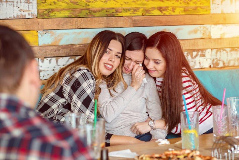 Amigos que consolam e que consolam a jovem mulher de grito que tenta fazer seu riso, conceito da amizade imagem de stock