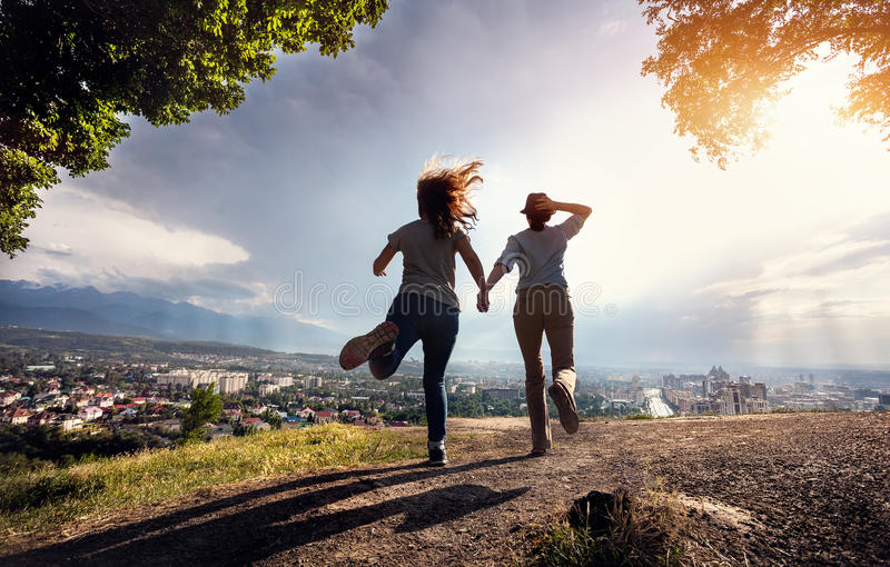 Amigos que corren al paisaje urbano en las montañas fotos de archivo libres de regalías