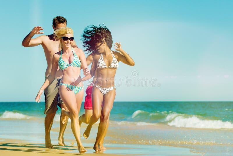 Amigos que corren el vacaciones de la playa fotografía de archivo libre de regalías
