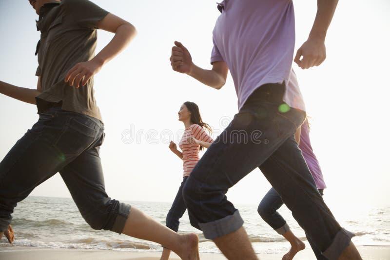 Amigos que corren en la playa fotografía de archivo