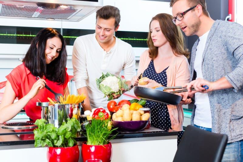 Amigos que cozinham a massa e a carne na cozinha doméstica imagens de stock royalty free