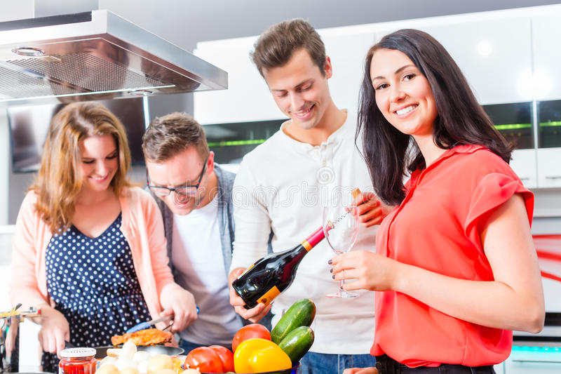 Amigos que cozinham a massa e a carne na cozinha doméstica fotos de stock