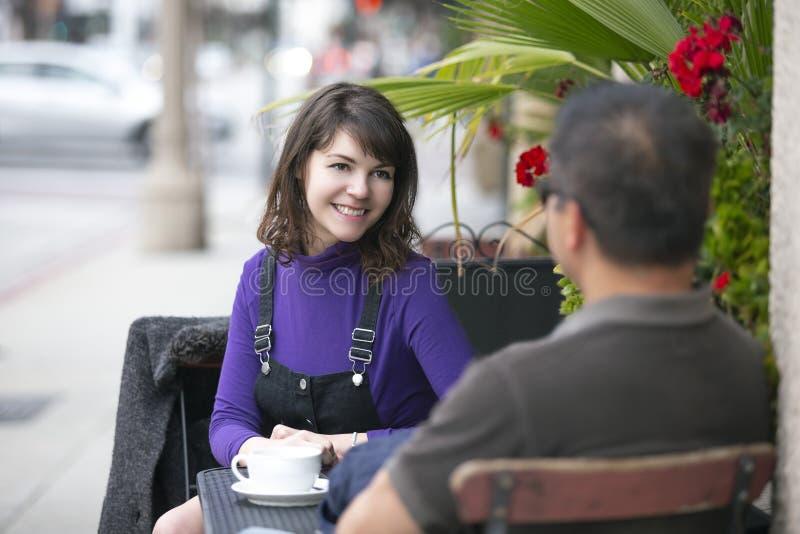 Amigos que cuelgan hacia fuera con café en un café de la acera o juntarse una fecha imágenes de archivo libres de regalías