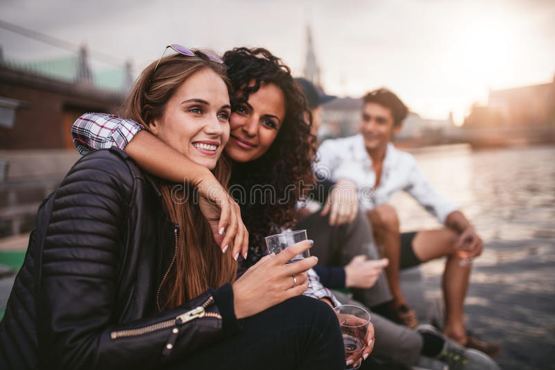 Amigos que cuelgan hacia fuera en el lago junto imagen de archivo