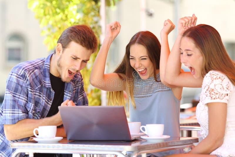 Amigos que dão um presente do portátil a uma menina surpreendida imagem de stock