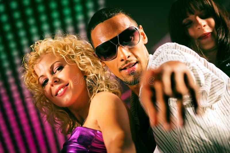 Amigos que dançam no clube ou no disco imagem de stock