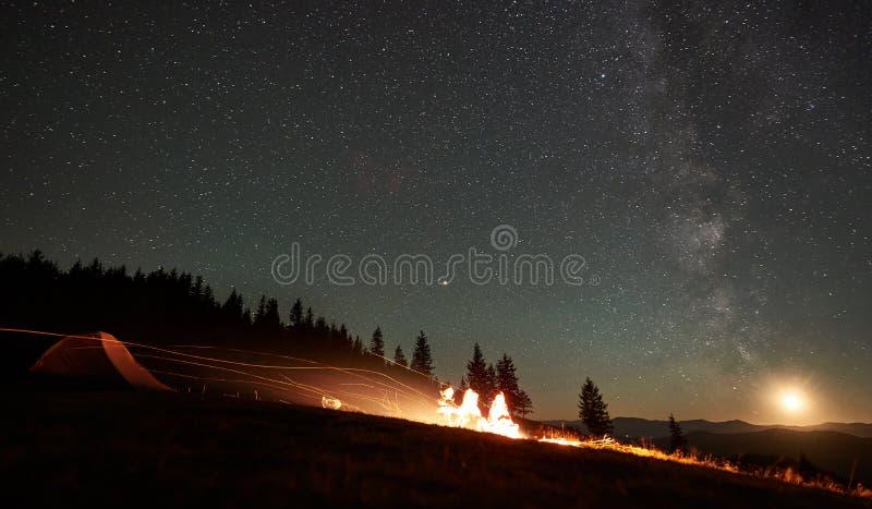 Amigos que descansam ao lado do acampamento, fogueira sob o céu estrelado da noite imagens de stock