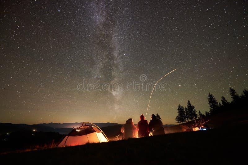 Amigos que descansam ao lado do acampamento, fogueira sob o c?u estrelado da noite foto de stock