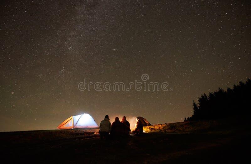 Amigos que descansam ao lado do acampamento, fogueira sob o c?u estrelado da noite foto de stock royalty free