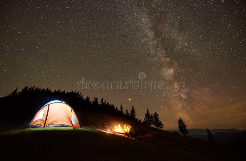 Amigos que descansam ao lado do acampamento, fogueira sob o c?u estrelado da noite imagens de stock royalty free