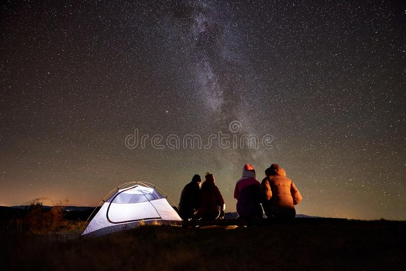 Amigos que descansam ao lado do acampamento, fogueira sob o c?u estrelado da noite fotografia de stock royalty free
