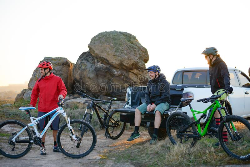 Amigos que descansam perto do caminhão de Off Road do recolhimento após a bicicleta que monta nas montanhas no por do sol Conceit fotos de stock