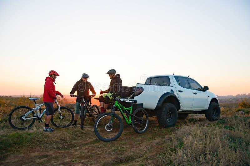 Amigos que descansam perto do caminhão de Off Road do recolhimento após a bicicleta que monta nas montanhas no por do sol Conceit fotografia de stock