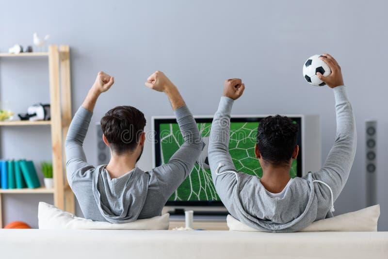 Amigos que disfrutan de fútbol en la TV imagen de archivo libre de regalías