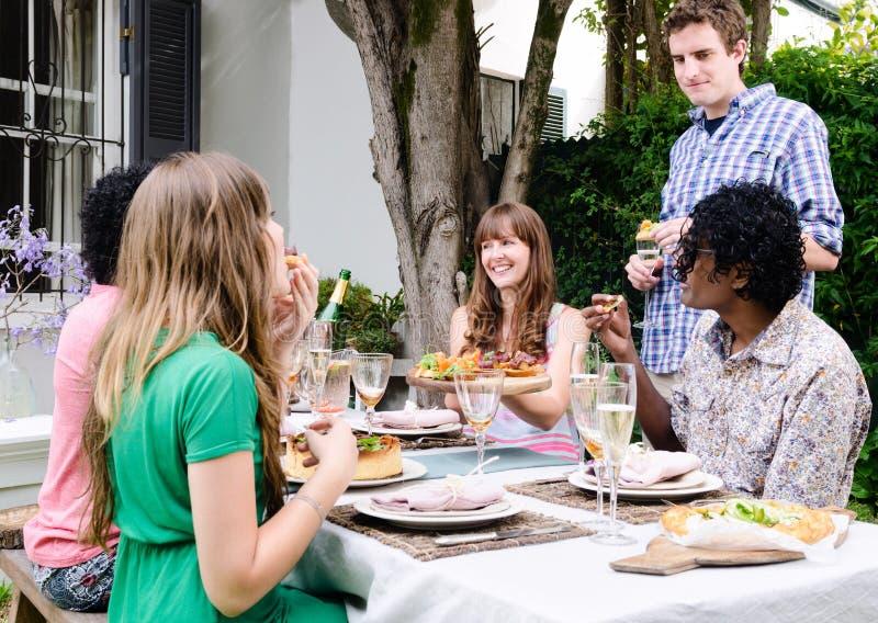 Amigos que disfrutan de la comida y de bebidas en una reunión imagen de archivo libre de regalías