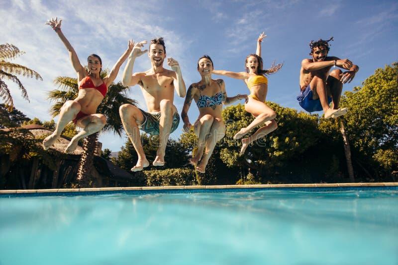 Amigos que disfrutan de la fiesta en la piscina imagenes de archivo