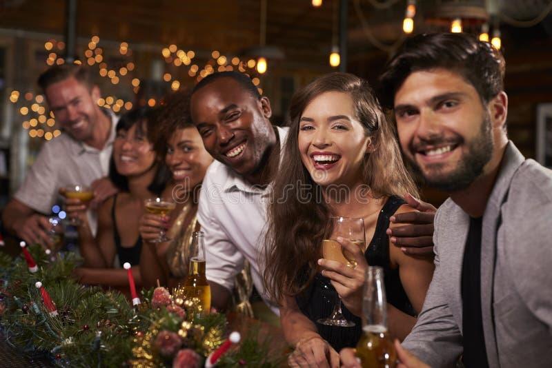 Amigos que disfrutan de mirada de las celebraciones de la Navidad a la cámara foto de archivo