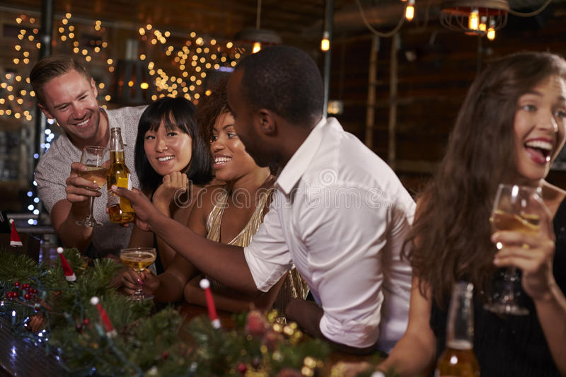 Amigos que disfrutan de una fiesta de Navidad en una barra que hace una tostada imágenes de archivo libres de regalías