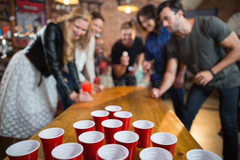 Amigos que disfrutan del juego del pong de la cerveza en barra imagen de archivo