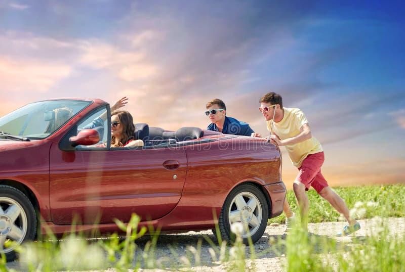 Amigos que empujan el coche convertible roto fotos de archivo