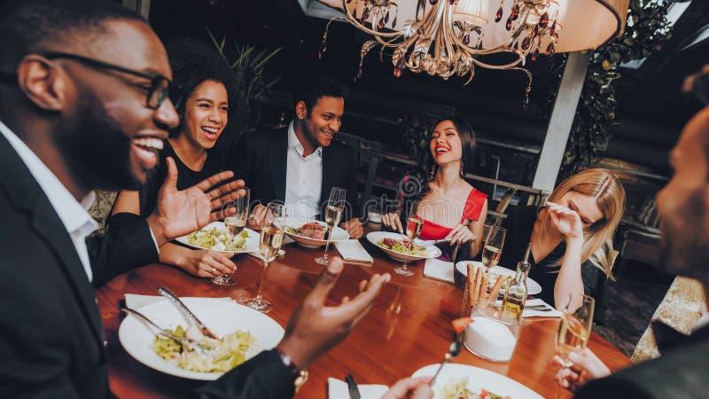 Amigos que enfrían hacia fuera disfrutar de la comida en restaurante imagen de archivo