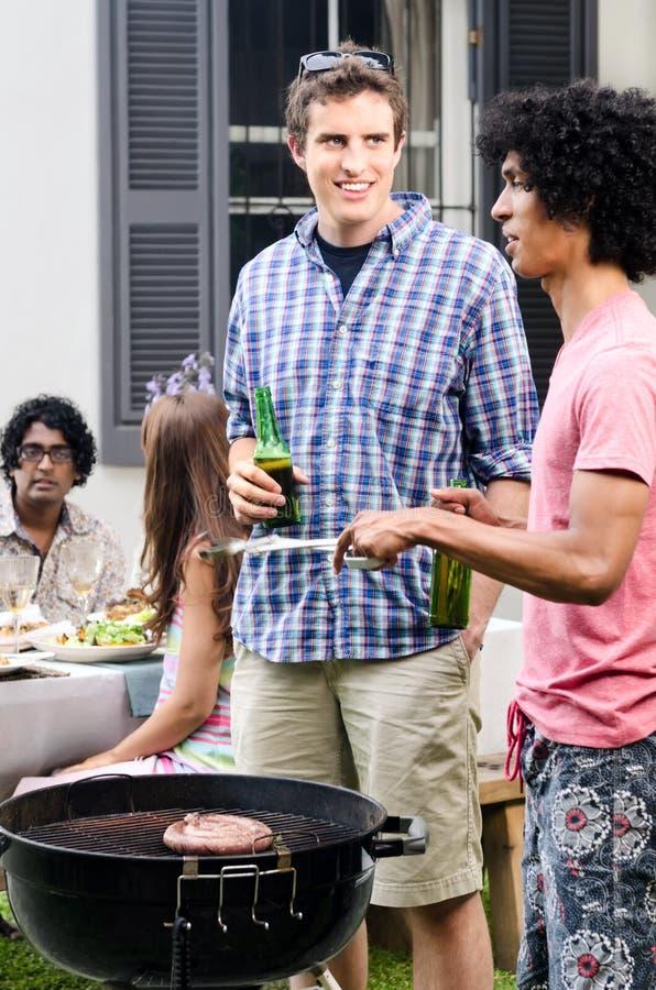 Amigos que enlazan sobre el Bbq con las cervezas a disposición imagen de archivo