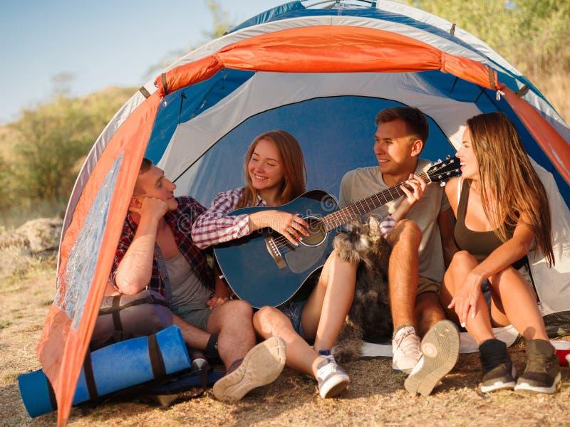 Amigos que escutam uma menina bonita que joga a guitarra em um fundo natural Acampamento com barracas Conceito ativo do estilo de imagens de stock royalty free