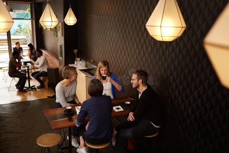 Amigos que falam ao apreciar o café fresco em um café junto foto de stock royalty free