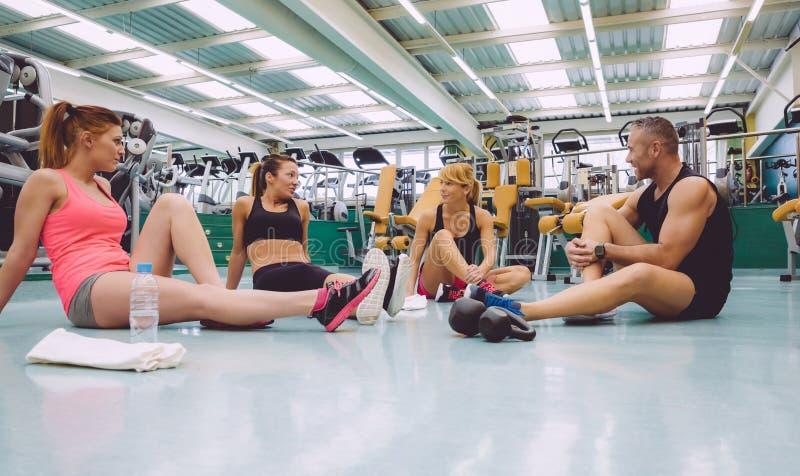 Amigos que falam no fitness center após a formação imagem de stock