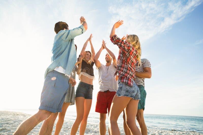 Amigos que fazem a elevação cinco na praia imagens de stock royalty free