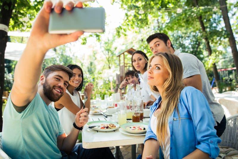 Amigos que fazem a foto do selfie no restaurante exterior fotos de stock