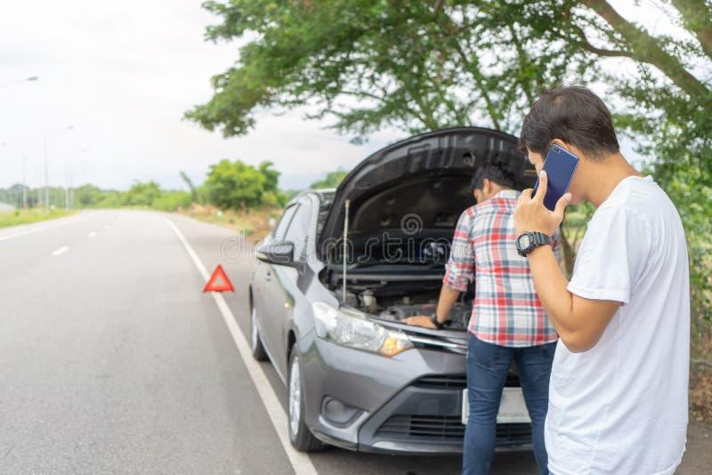 Amigos que fixam o carro dividido na estrada que chama para a ajuda no telefone celular Dois amigos do homem que falam no telefon foto de stock royalty free