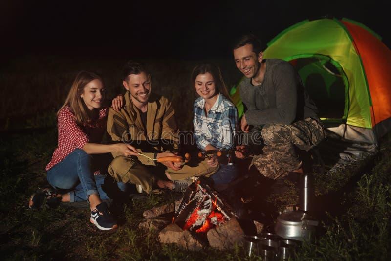 Amigos que fritam salsichas na fogueira na noite imagem de stock