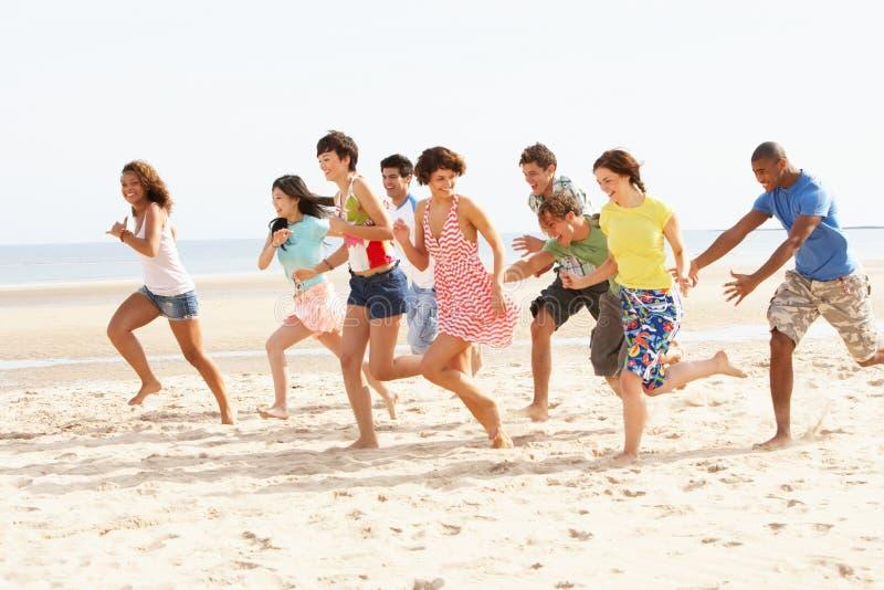 Amigos que funcionam ao longo da praia junto imagem de stock