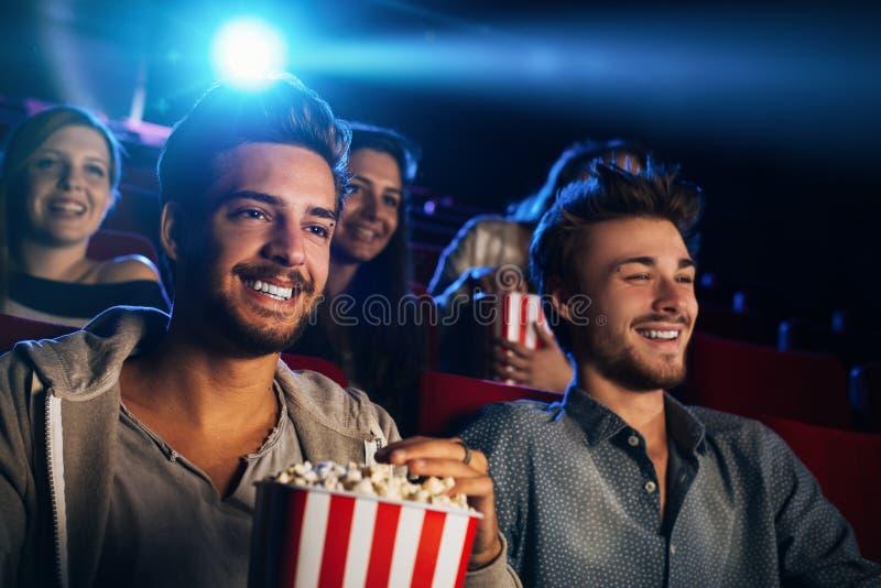 Amigos que gozan en el cine foto de archivo