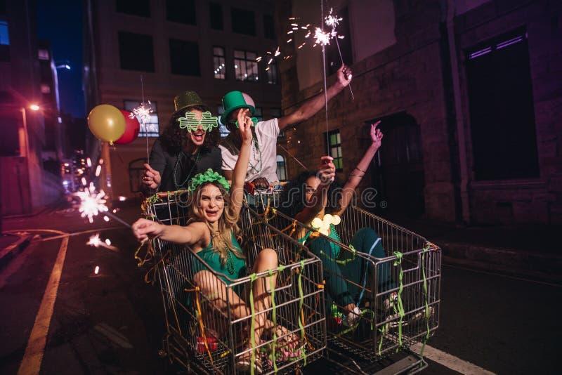 Amigos que gozan en la celebración del día del ` s de StPatrick hacia fuera en la calle imagen de archivo libre de regalías