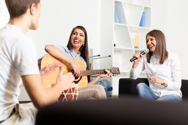 Amigos que gozan tocando la guitarra y cantando junto foto de archivo