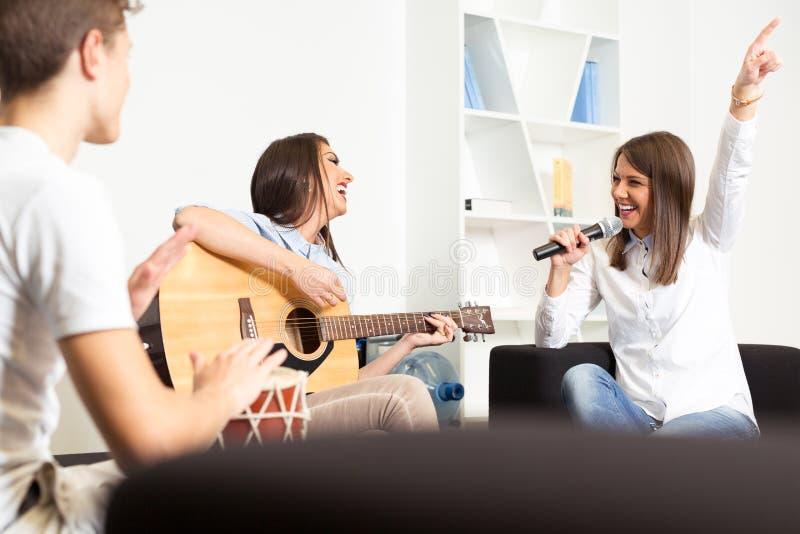 Amigos que gozan tocando la guitarra y cantando junto imágenes de archivo libres de regalías