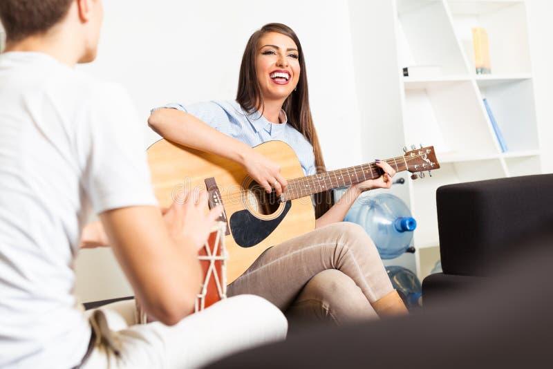 Amigos que gozan tocando la guitarra y cantando junto imagenes de archivo